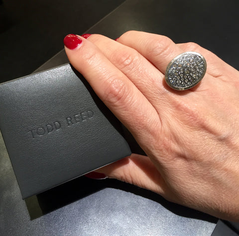 "Palladium and Sterling silver todd reed starry night ring on finger. Hand is holding a grey box imprinted with ""Todd Reed"""