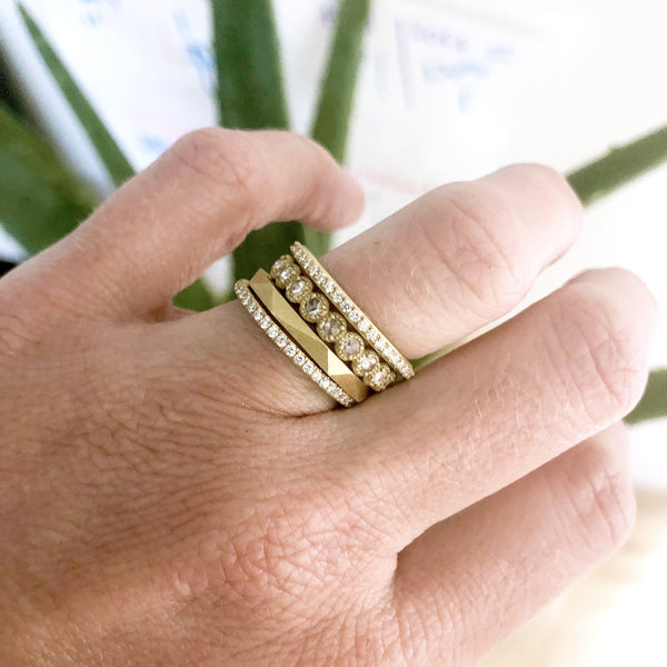 Four yellow gold and diamond rings on finger by Samantha Louise