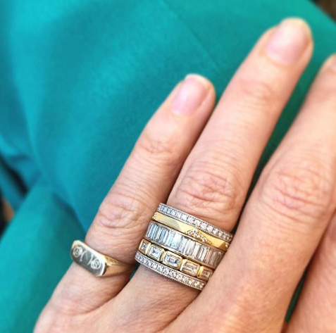 Woman's hand wearing 18K yellow gold thin Geo band with pave set diamonds. Hand also wearing five other mixed metal rings.