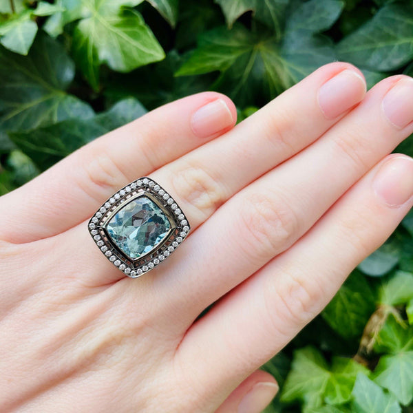 18K white gold ring with black rhodium finish, cushion aquamarine and diamonds, on hand with green leaf background