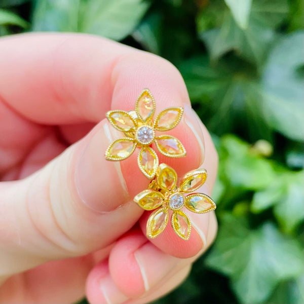 18K yellow gold flower stud earrings with yellow sapphires and diamonds, held by hand with green background