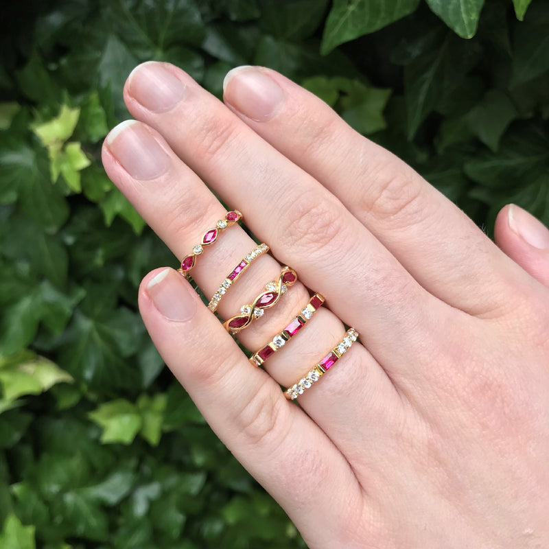 Five 18K yellow gold Suwa ruby and diamond rings on one finger, green background