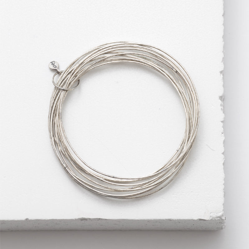 Zuzko Stacked bracelet with 13 textured sterling silver thin stacked bangles secured with small loop