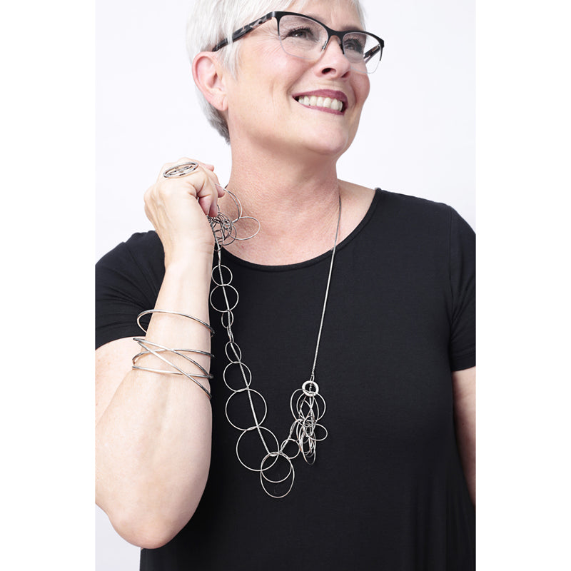 Woman wearing Zuzko 3 in 1 necklace with large silver circles in semi circle and matching bracelet against black shirt