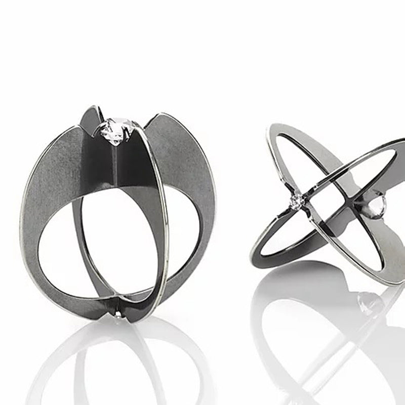 Two Zuzko Clutch Atom rings in oxidized sterling silver with one small and one large round white topaz at top and bottom, in unique shape of hydrogen atom. One ring is standing, the other is on its side
