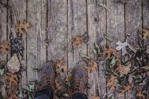 boots on wooden leafy deck