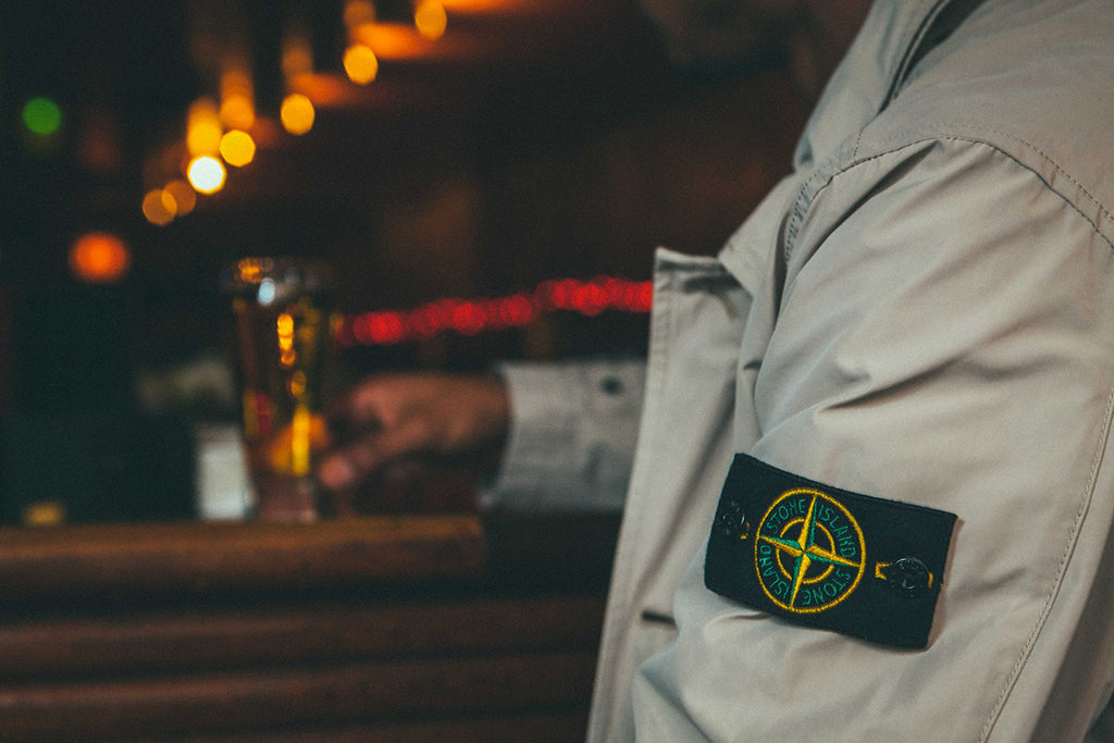 Sitting at bar wearing Stone Island 70422 Micro Reps Long Coat
