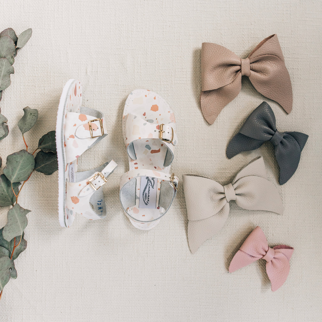 leather sandals and bows featured in terrazzo, sand, heron, fog, and peony