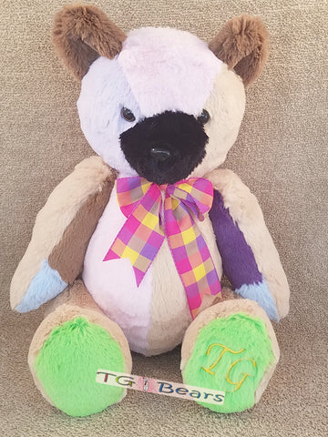 Patch Bear wearing a multicolored coat and plaid ribbon.