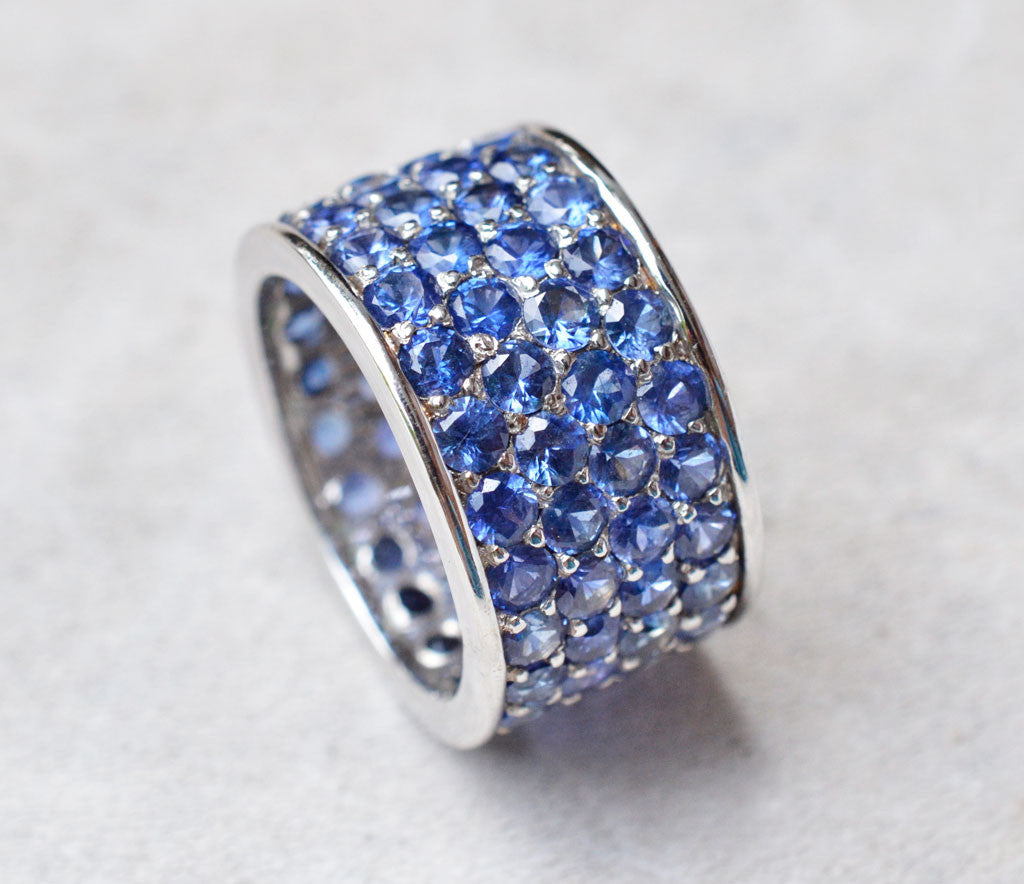 Thick band ring with four rows of blue sapphires paved in 18K white gold