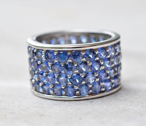 18K white gold ring with a thick band studded with four rows of blue sapphires