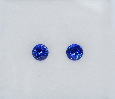 A pair of dark blue round shaped blue sapphires