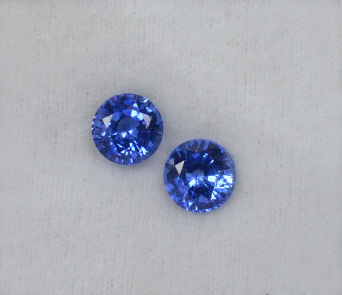 A pair of medium blue round shaped blue sapphires