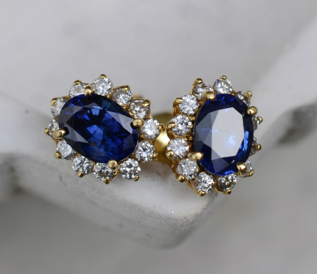 Natural Ceylon Blue Sapphire center piece earrings surrounded by 24 diamonds set in 18K carat yellow gold available at Elizabeth Jewellers in Sri Lanka