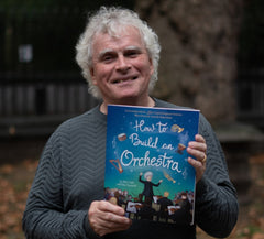 Sir Simon Rattle with the childrens' book How to Build an Orchestra