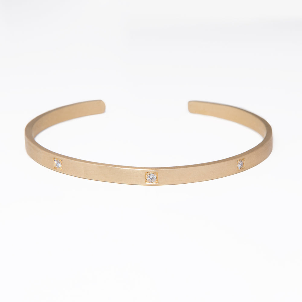 WD487, 14kt gold with slight hammered detail squared oragnic cuff with 3 diamonds.