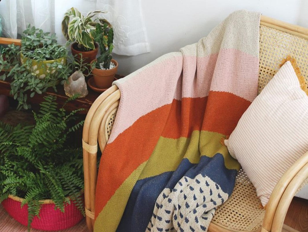 A colourful Calhoun and Co throw drapes over the arm of a rattan chair in a comfy corner filled with light and plants