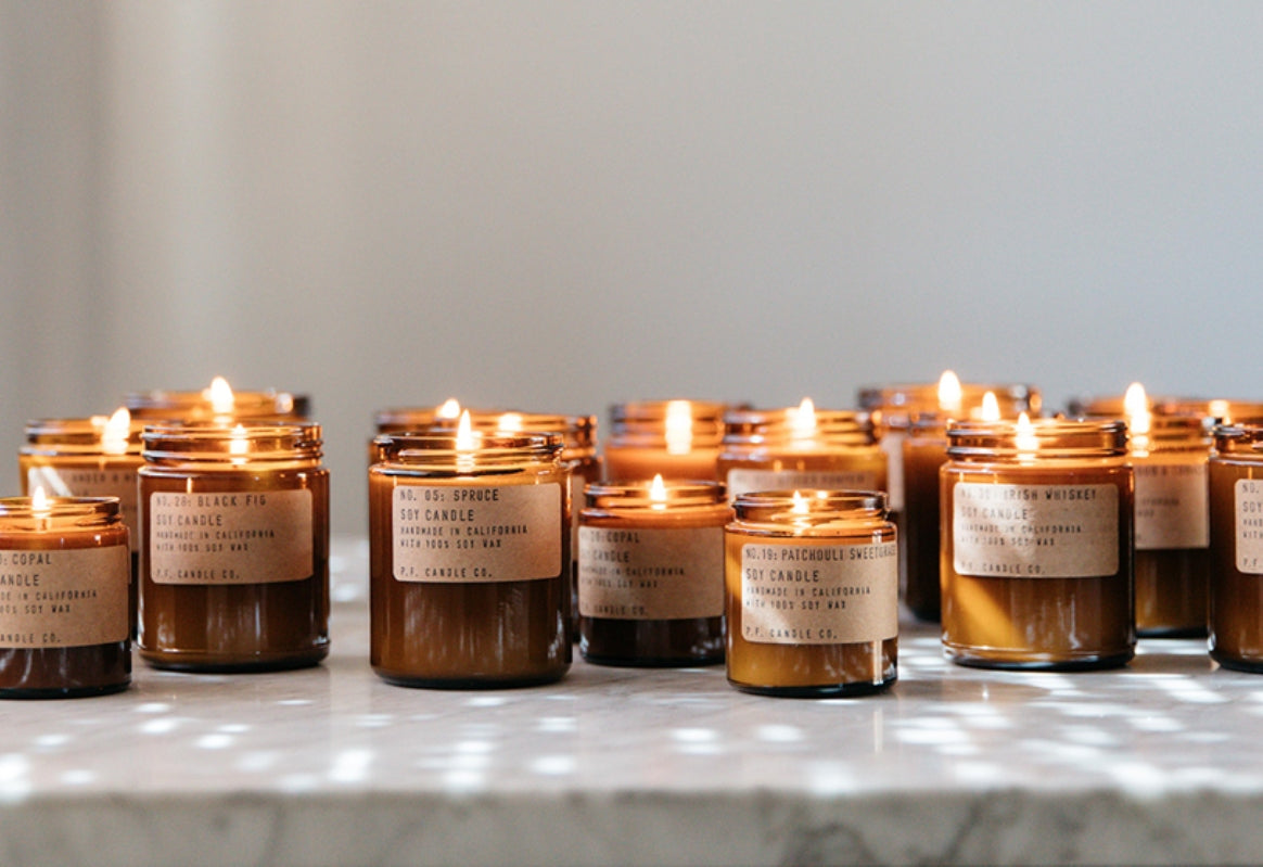 Rows of amber glass soy candles with simple kraft labels offer a warm light, resting on a marble countertop