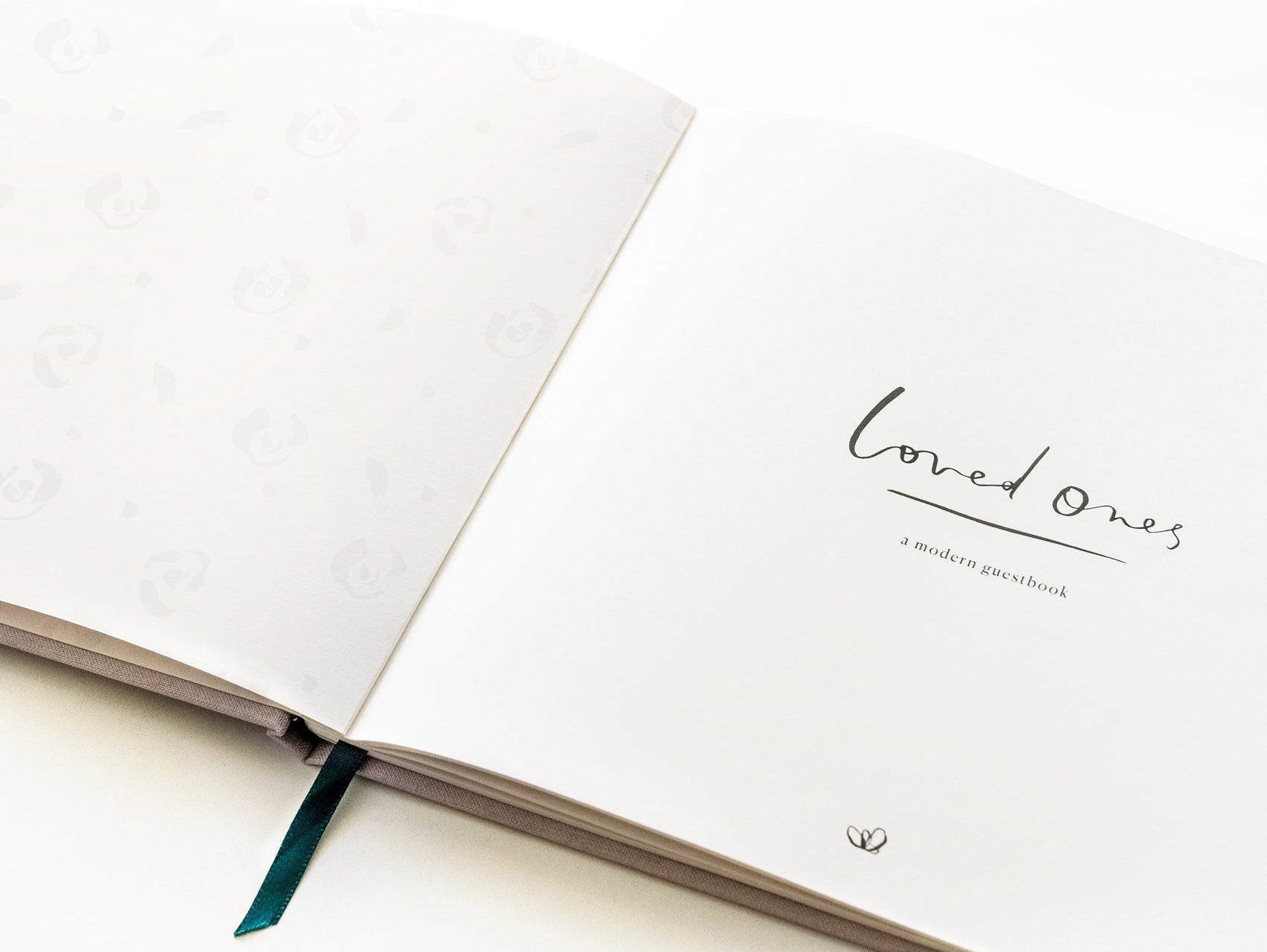 Loved Ones guest book by Our Heiday opened to title page on brilliant white background with satin forest green ribbon bookmark