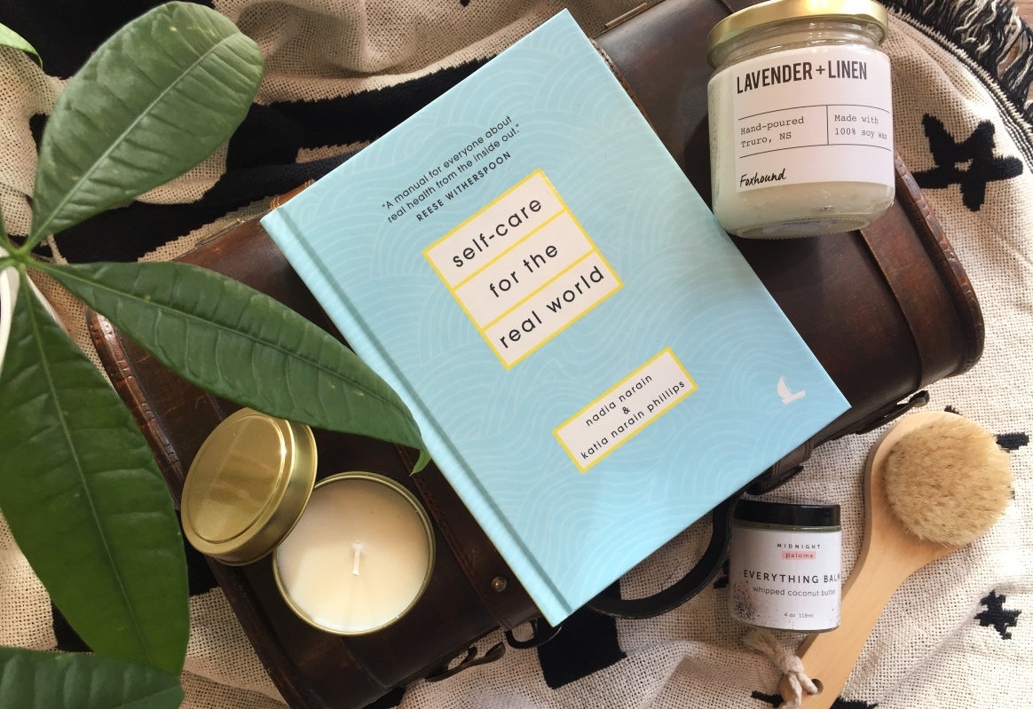 Aqua blue and yellow Self-Care for the Real World book sits between two candles on top of an ivory and navy blanket with green plant leaves hanging over the corner