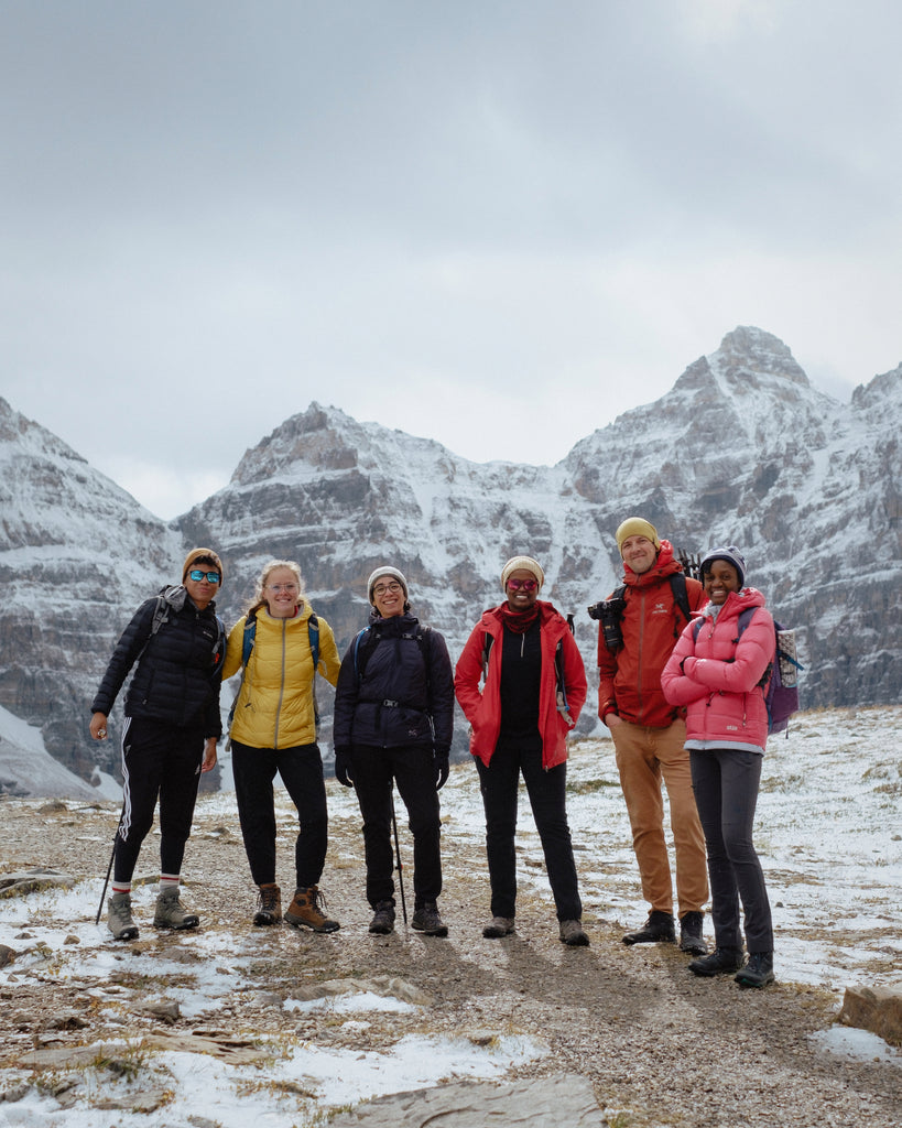BIPOC hikers and allies stand smiling in front of a wintery mountainscape while on a hike exploring with Colour the Trails
