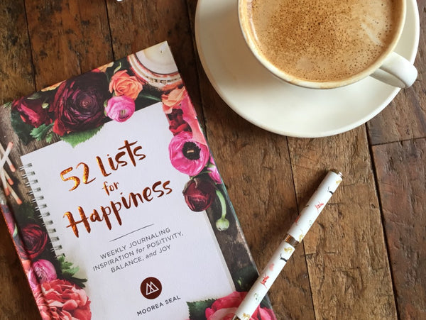Flat lay of 52 Lists for Happiness on a wooden table with a latte in soft morning light