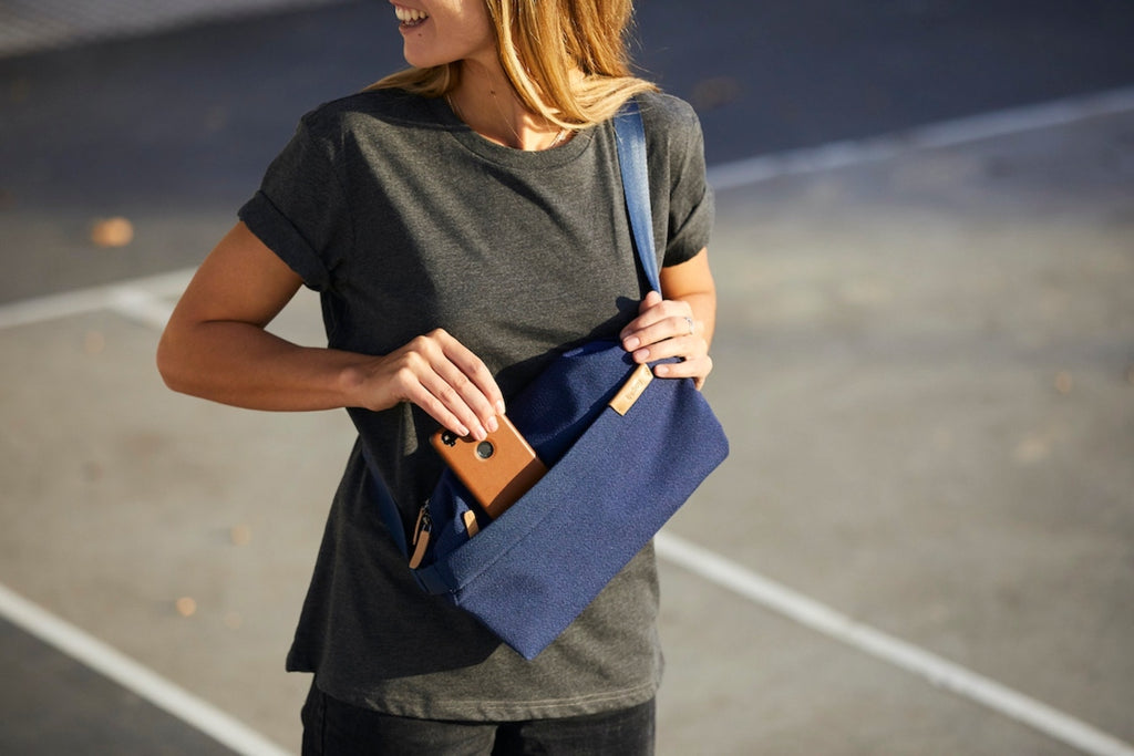 White female stands in a parking lot slipping a cell phone into their crossbody City Pouch by Bellroy