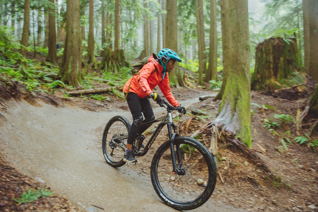 Judy Milay takes on the trails on a mountain bike amongst a forested backdrop on Canada's west coast