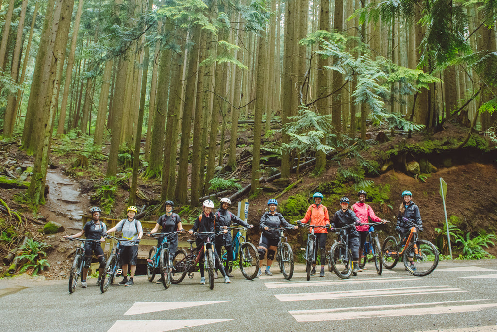 Group of BIPOC persons and allies stand with mountain bikes at the start of a forested trail ride