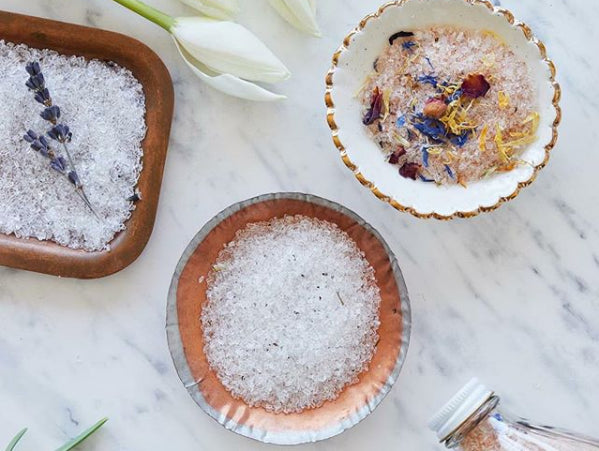 Flatlay of three ceramic bowls containing Dot and Lil bath salts with dried flowers on a marble counter.