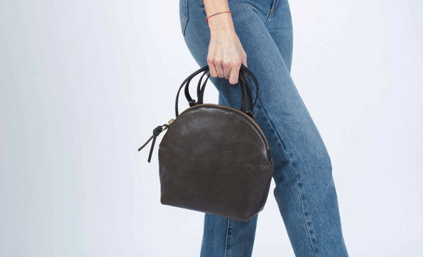 Woman wearing jeans holding a black Eleven Thirty Anni bag with a circular top, flat bottom, and single top handle