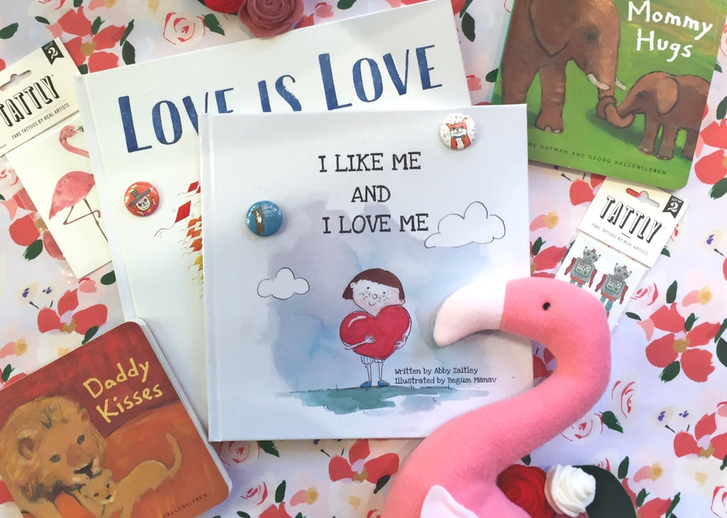 Flat lay of gift ideas for the kids for Valentine's Day including lots of books and a bright pink stuffed flamingo