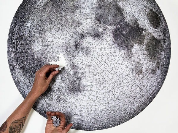 Two hands piecing together Four Point Puzzles' circular moon puzzle