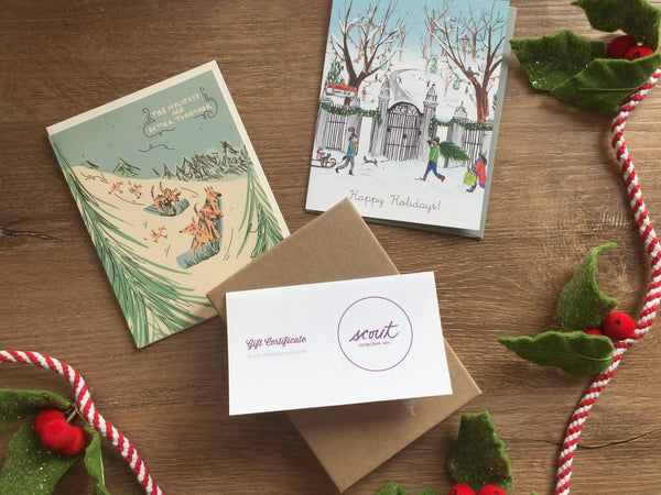 Flat lay of two holiday cards and a Scout gift certificate on a wooden backdrop with a festive rope decorated with felt mistletoe