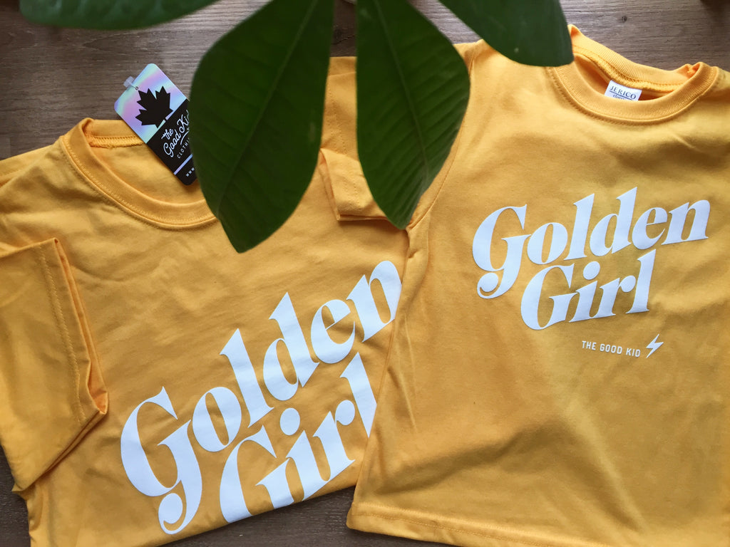 Flat lay of two folded bright yellow t-shirts with Golden Girl scripted across the front in white, one t-shirt in a child's size, one in an adult size