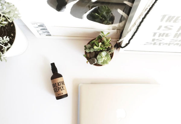 Flat lay of an amber Happy Spritz aromatherapy bottle on a white desk with simple modern black and white home decor surrounding