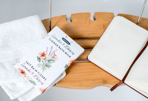 A cozy Dot and Lil bath sachet flat lay on a bathtub organizer with a soft white towel and opened notebook.