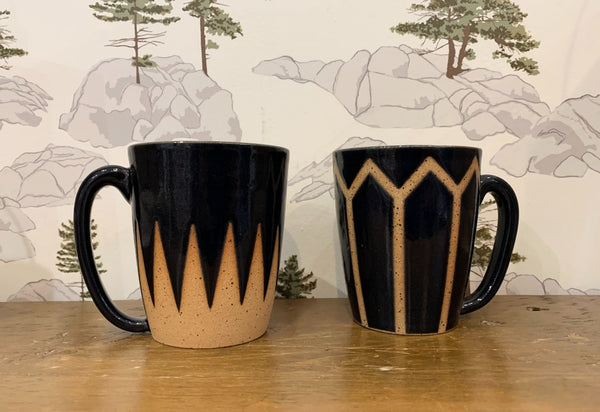 Two clay and deep navy handmade ceramic mugs sit on a wooden bench with a Canada Shield wallpaper design as the backdrop