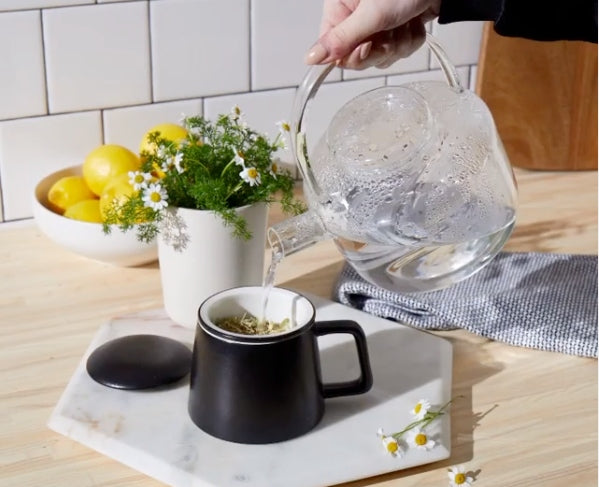 Hand pouring boiling water from a glass kettle to brew a cup of chamomile tea