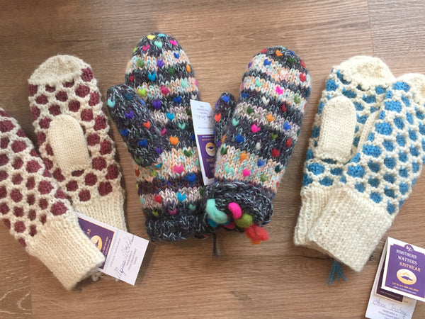 Three pairs of Northern Watters knit mittens laid in a row