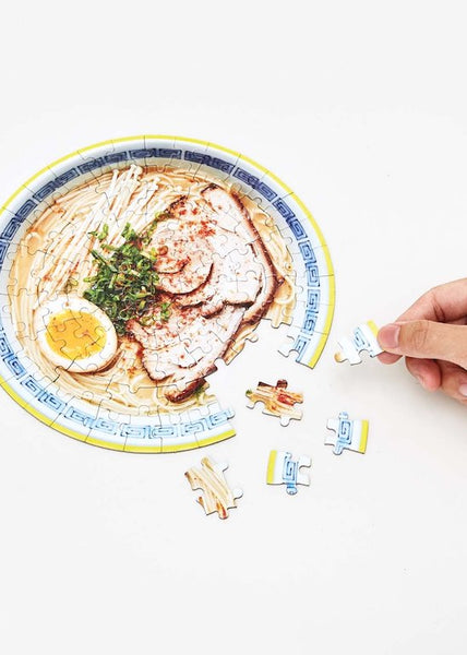 A hand working on a round ramen puzzle