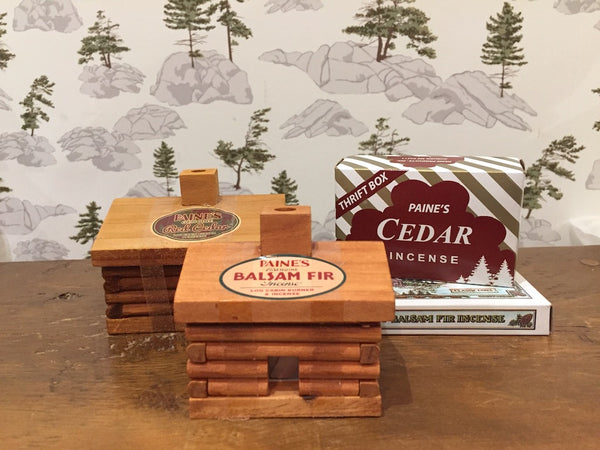 Paine incense cabins sit on a bench in front of a wallpaper featuring an outdoor scene inspired by the Canadian Shield