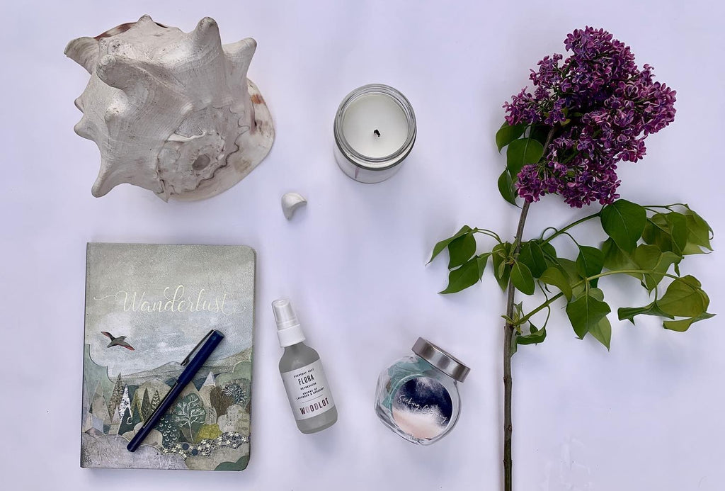 Photo of ceremonial objects in a flatlay format featuring a lilac branch, conch shell, journal, and aromatherapy items