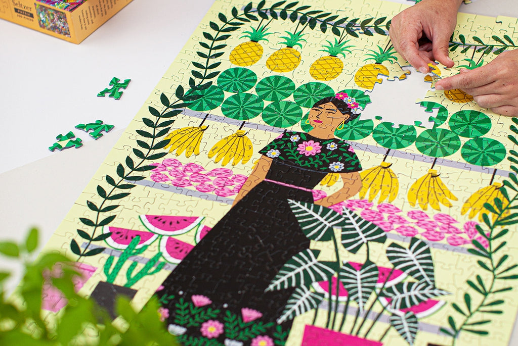Seltzer Fruit Lady puzzle in progress lays on a white background with a green plant in the foreground