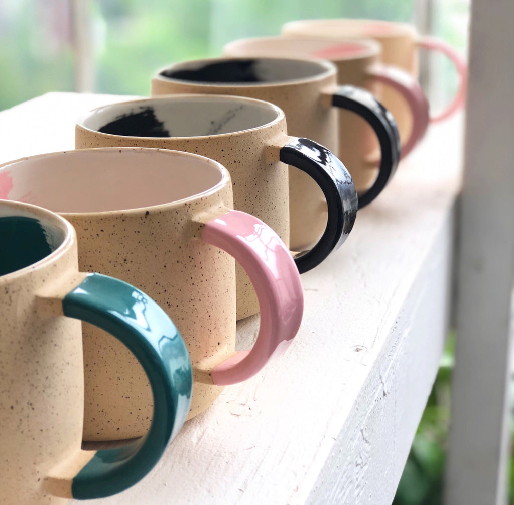 Line-up of Shayna Stevenson's signature ceramic brushstroke mugs in green, black, and pink