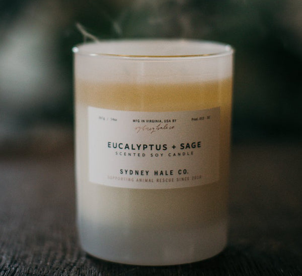 Sydney Hale eucalyptus and sage soy candle in a frosted glass container sitting on a wood table with soft plumes of smoke