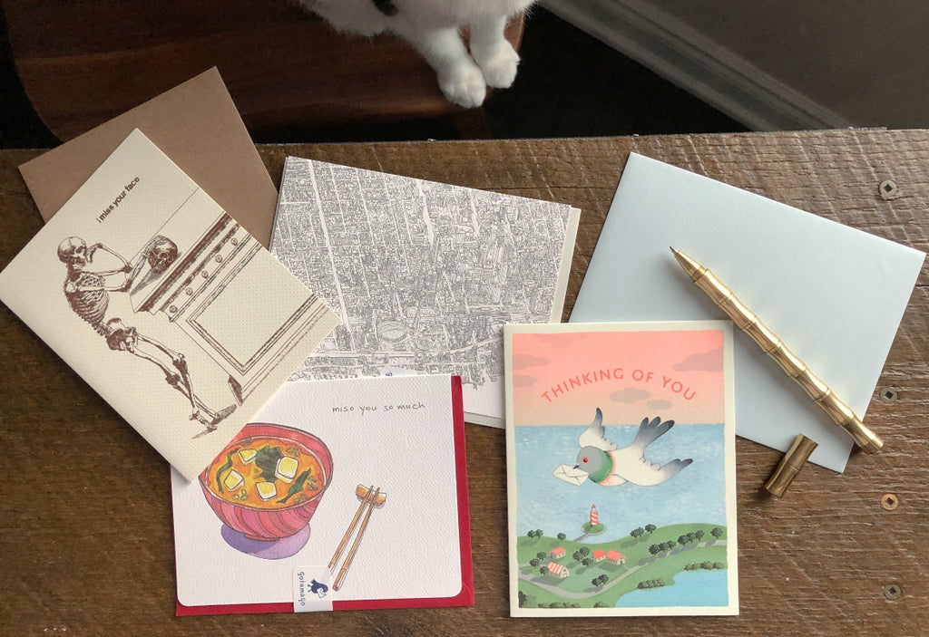 Greeting cards and envelopes lay strewn on a small wooden table with a golden pen set to the side and the white paws of a cat in the corner of the photo