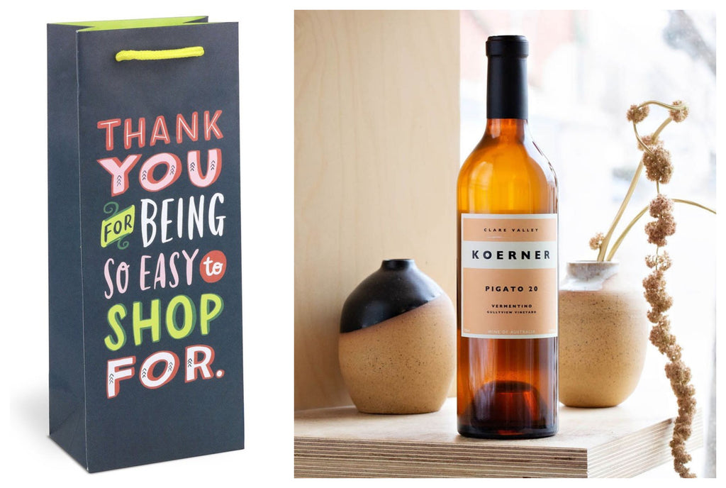 Product photo of wine gift bag that reads 'Thank you for being so easy to shop for' with a photo of a bottle of rose wine beside placed on a stone surface with botanicals in the background