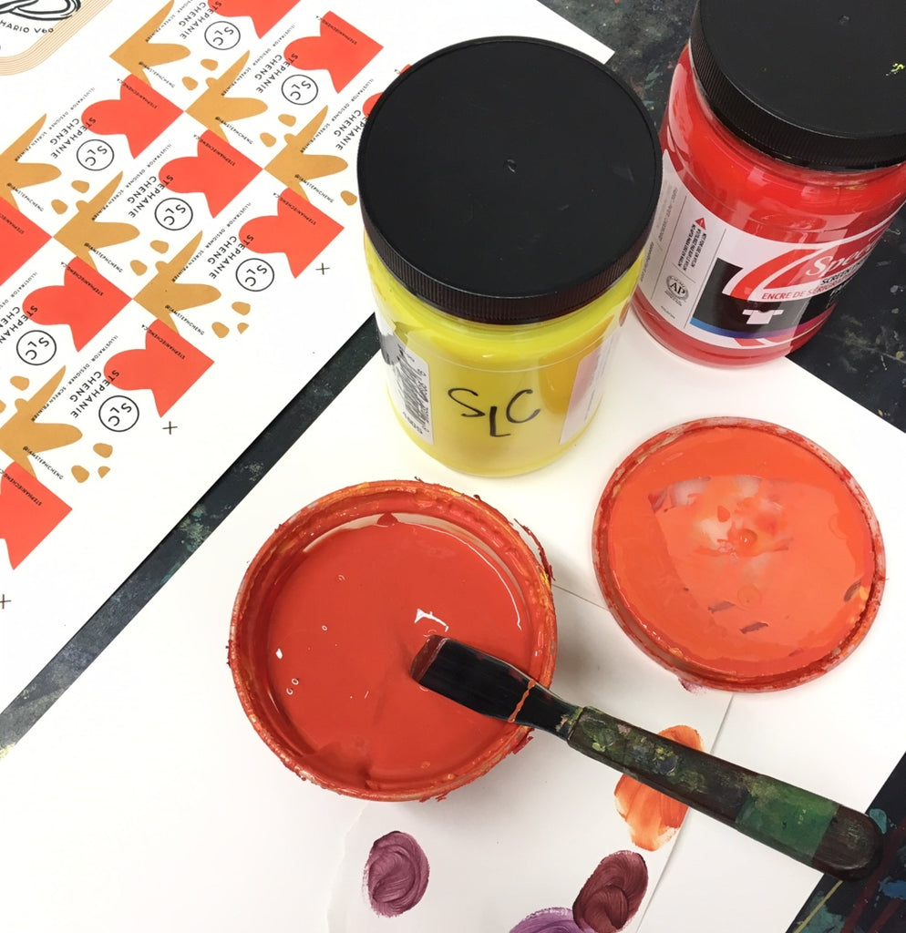 Paints and paint swatches sit alongside screen printed and colourful business cards by Stephanie Cheng