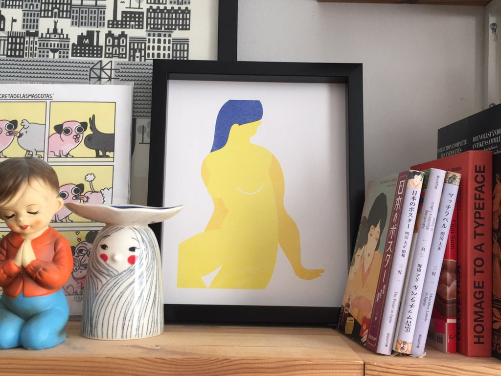 Stephanie Cheng's woman print, available at Scout, framed and displayed on a shelf filled with vintage trinkets and art books